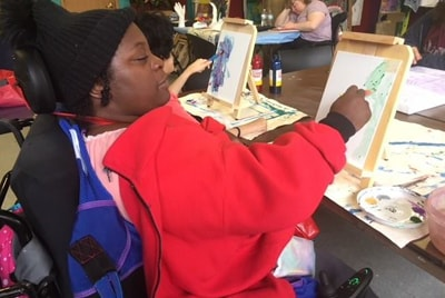 A woman sitting and working on an art project with supplies from items donated to the Anixter Center.
