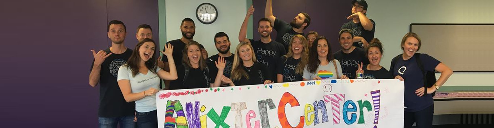 A group of Anixter Center helpers holding up a homemade sign that says Anixter Center!