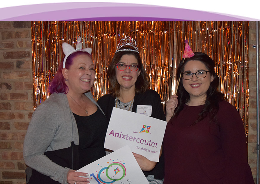 Three women having fun at the Winter Warm Up event holding Anixter Center signs and smiling.