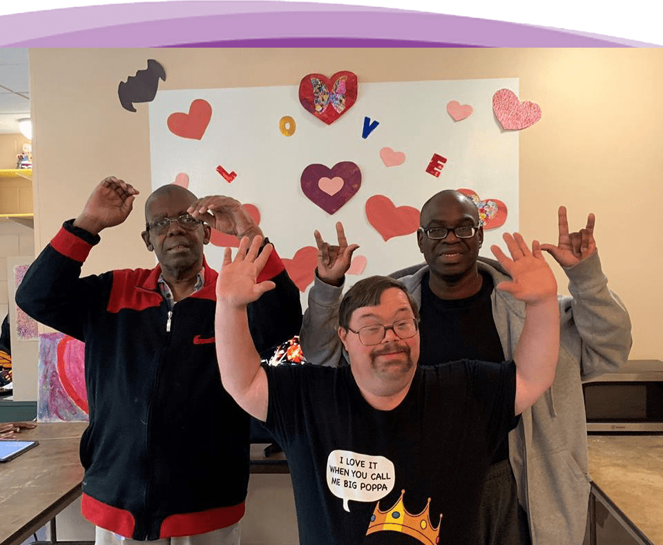 Three happy Anixter Center clients with their hands in the air. The background has really nice artwork that says Love