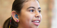 A young girl that has a hearing aid is looking at us and smiling.