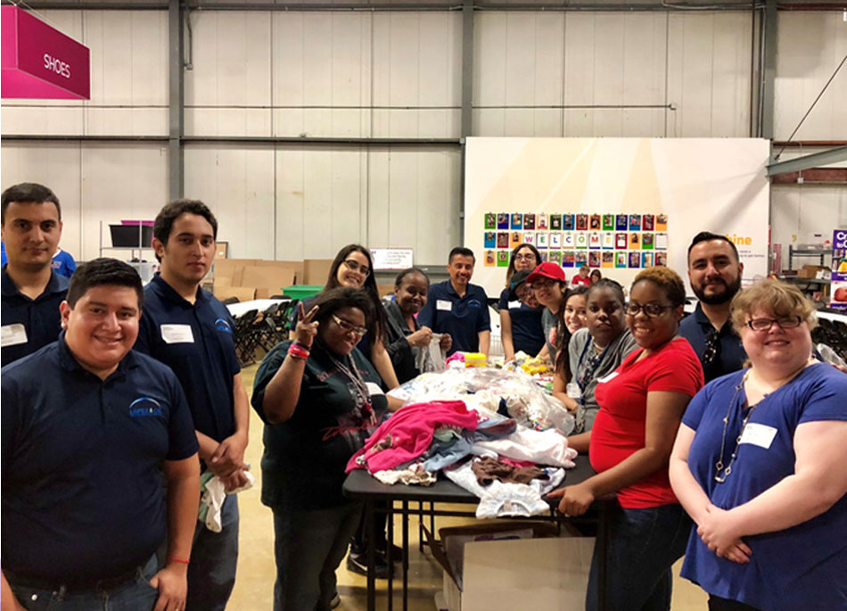A happy group of volunteers and Anixter Center clients sorting clothing.