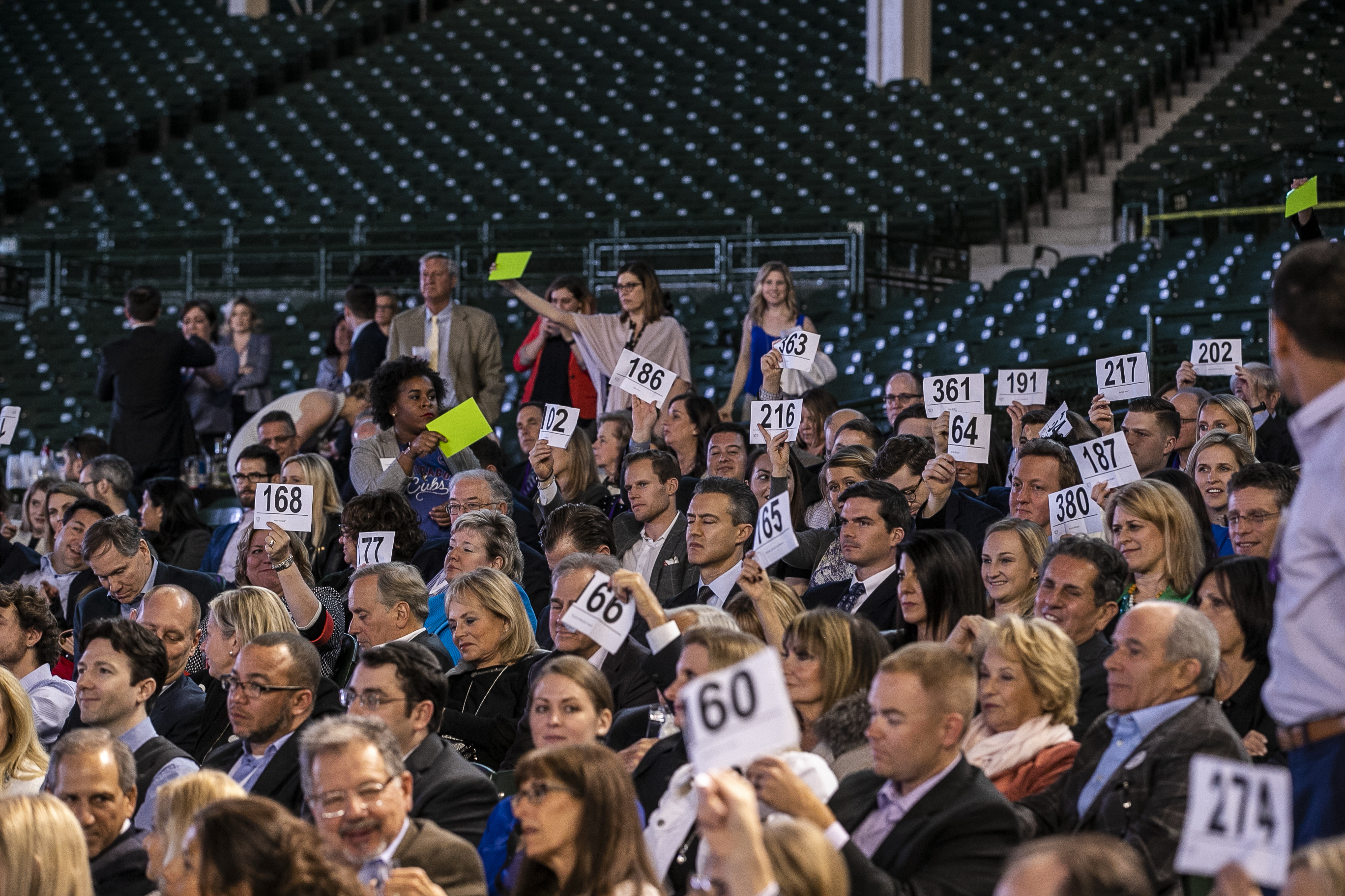 Gala guests bidding at the auction in the Wrigley Field stadium