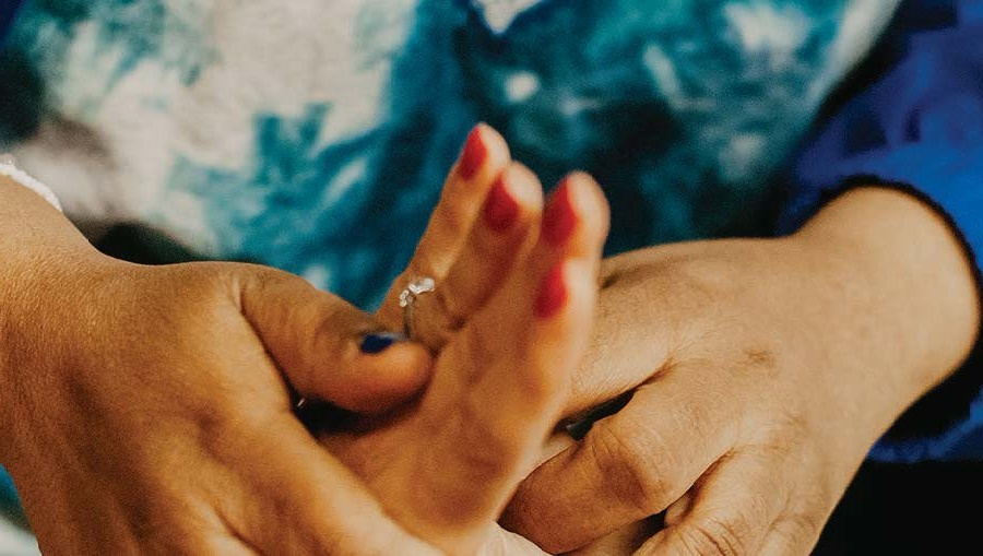 A close up view of two people holding hands in support.