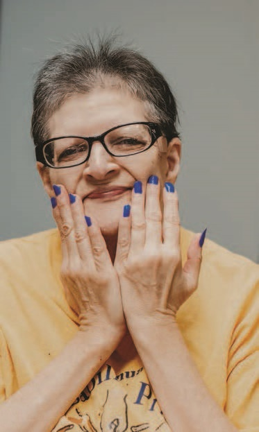 Smiling female CMH client with blue nail polish.