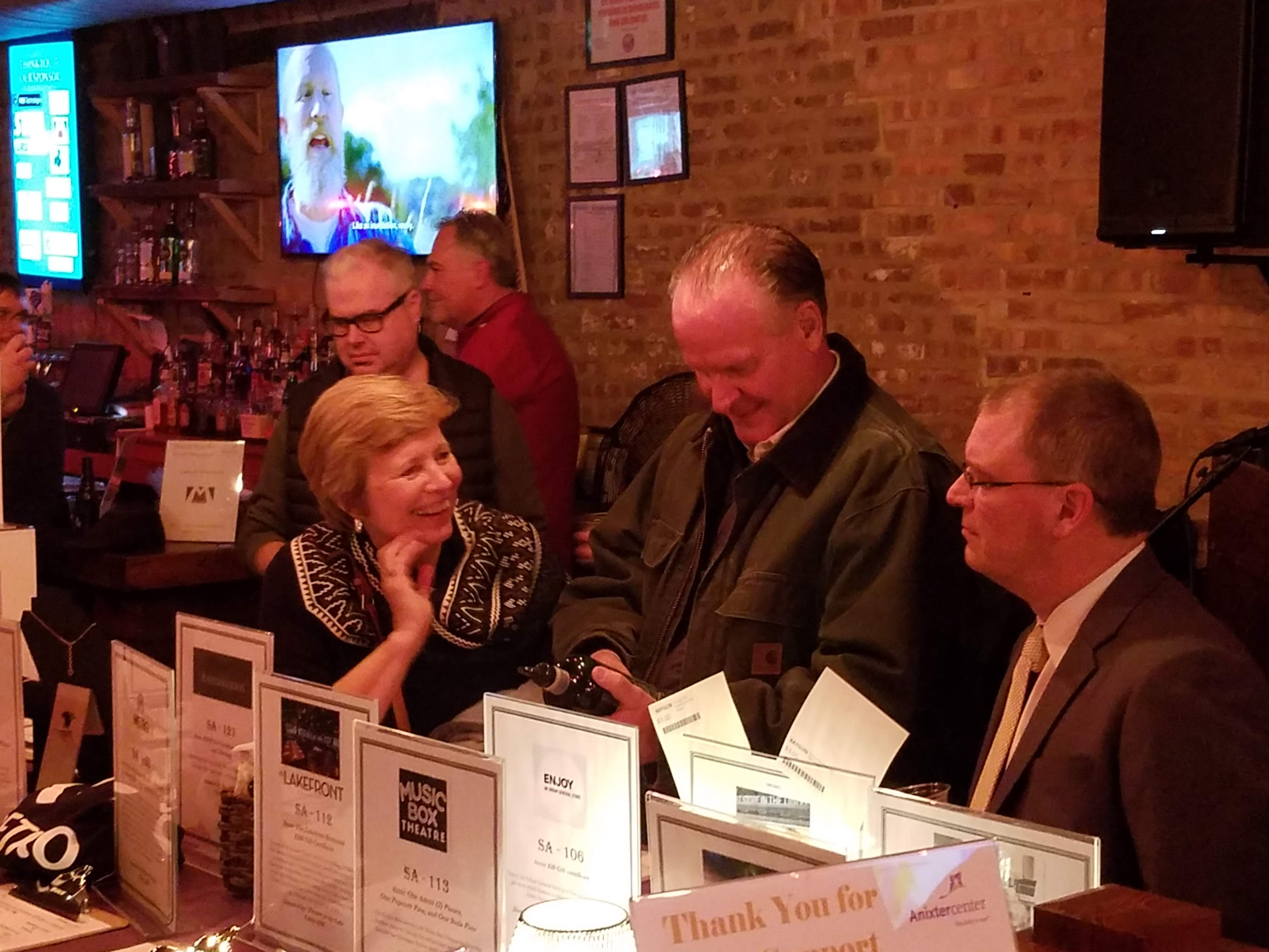 Three guests placing their bid on the silent auction items at the 2020 Winter Warm Up.