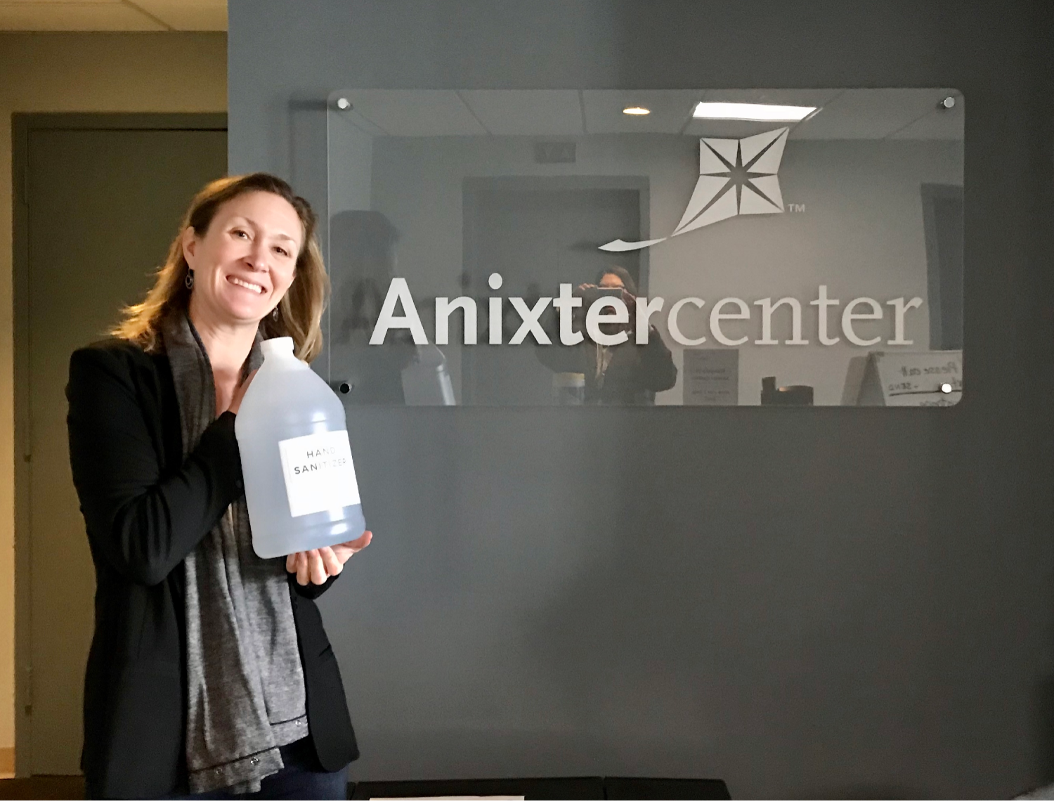 Anixter Center President & CEO posing in front of the Anixter Center sign with a gallon of the homemade sanitizer created and donated by KOVAL Distillery.